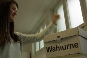 Schülerin wirft ihren Wahlzettel in die Wahlurne
